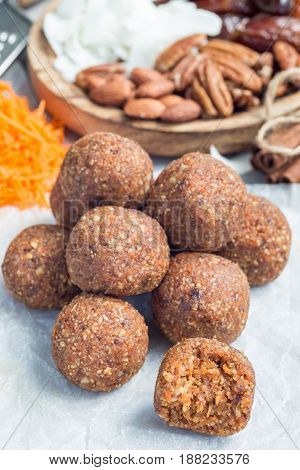 Healthy homemade paleo energy balls with carrot nuts dates and coconut flakes on parchment vertical