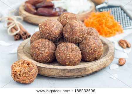 Healthy homemade paleo energy balls with carrot nuts dates and coconut flakes on wooden plate horizontal