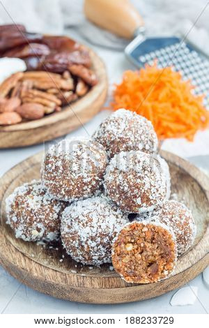 Healthy homemade paleo energy balls with carrot nuts dates and coconut flakes on wooden plate vertical