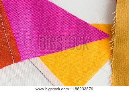 quilting, sewing, tailoring and fashion concept - beautiful colored patchwork fabric, red, yellow, purple stitched textile scraps at workshop, flat lay, top view
