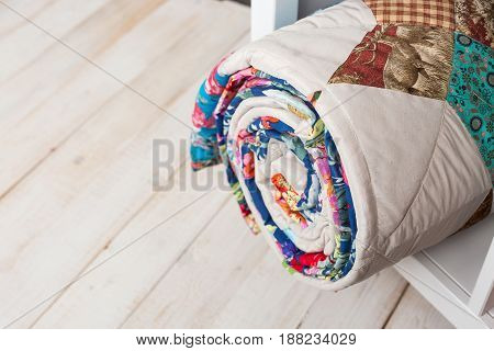 patchwork, sewing and fashion concept - cute colorful quilted blanket at white shelves with storage compartment in studio, white floor in a warehouse of finished products, top view