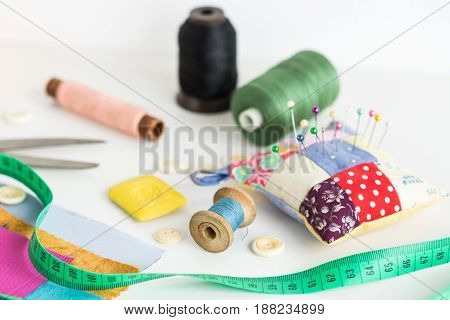 sewing tools, patchwork, tailoring and fashion concept - close-up on white desk with scissors, pincushion, pieces of colored patchwork fabric, soap, measuring meter, thread spools, buttons
