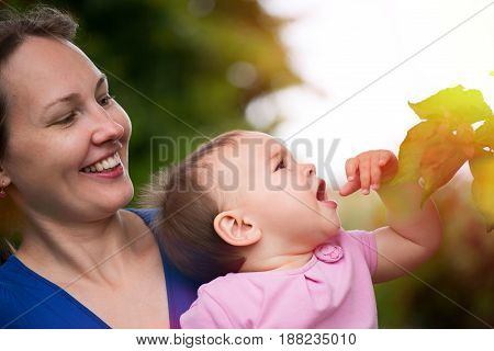 Mother And Little Baby Daughter Touching Leaves Of Tree In Summer In Nature