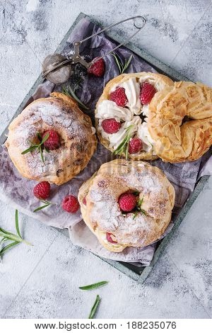 Homemade choux pastry cake Paris Brest with raspberries, almond, sugar powder and rosemary, served on wooden serving tray over gray blue texture background. French dessert. Top view
