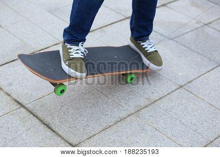 closeup of skateboarder legs skateboarding at outdoor