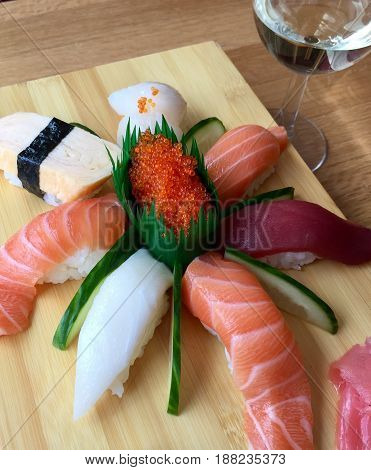 Sushi dinner in a Japanese restaurant. A plate of nigiri sushi and with salmon, tuna, scallop, snapper, cucumber and a glass of wine