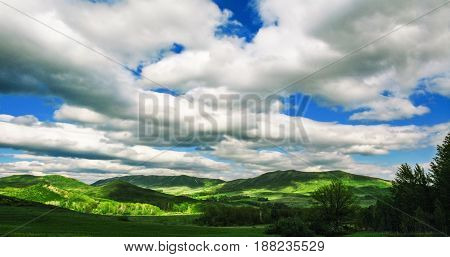 Panoramic mountain landscape with clouds in blue sky