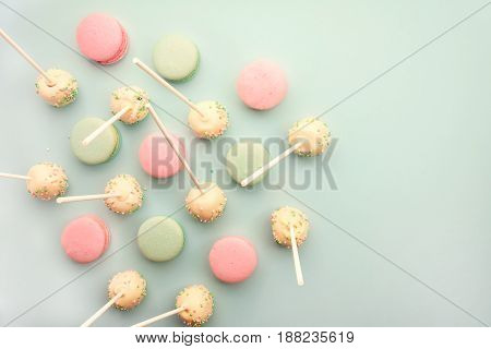 Colorful macaroons mixed with cake pops on sticks. Flat lay with copy space