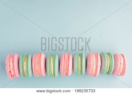 Sweet colorful macaroons in row on blue background with copy space. Flat lay