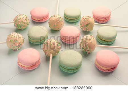 Closeup of sweet macaroons with cake pops or cake crumbs with icing on sticks