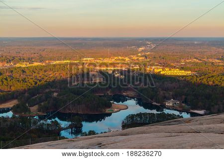 Aerial view of forest park settlements and huge shadow from the top of Stone Mountain at sunset Georgia USA