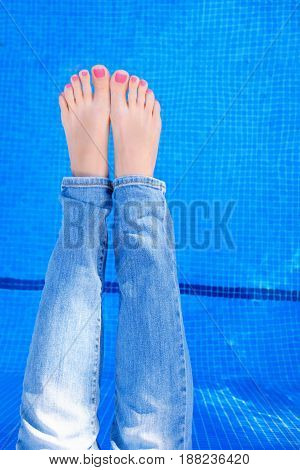 Above view on woman wearing blue jeans while relaxing by the swimming pool. Top view of female legs