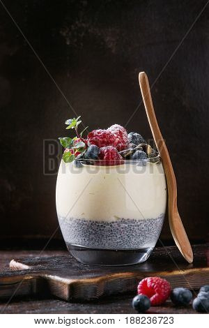 Dessert breakfast layered chia seeds pudding, rice porridge in glass decorated by fresh blueberries, raspberry, mint. Stand with wooden spoon on dark serving board over black texture background.