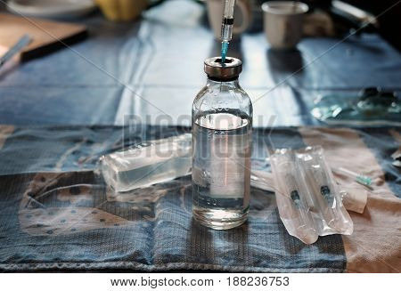 Bottle with abstract medicine treatment liquid and syring on the top a messy kitchen in the background