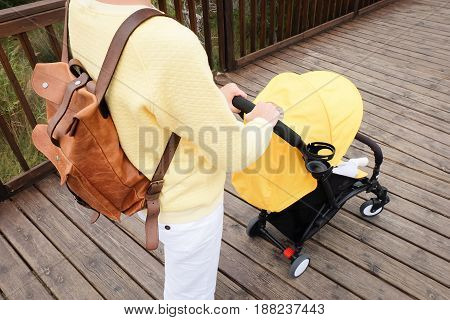 Close-up of woman strolling a carriage with a baby on wooden bridge outdoor