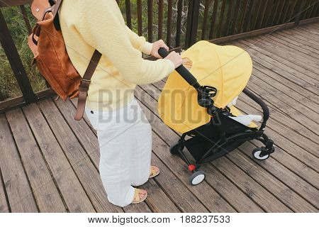 Mother pushing a carriage with a baby outdoors. Closeup shot