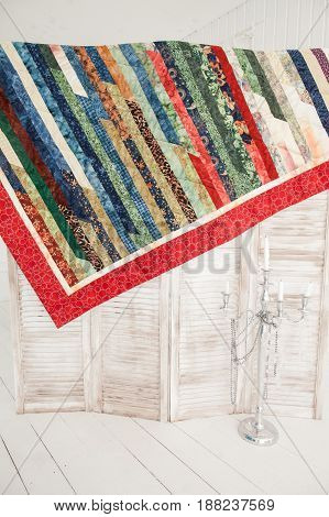 Patchwork quilt hangs on a wooden screen. Part of patchwork quilt in a white room.