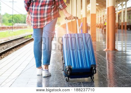 Asian women tourist is dragging a blue suitcase with wheels on the train platform.