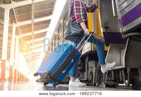 Asian women tourists are hauling a blue suitcase with wheels on the train.