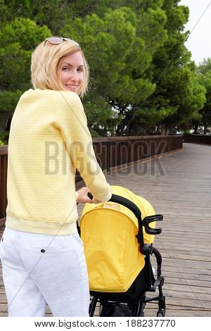 Smiling mother strolling a baby in carriage outdoors in park