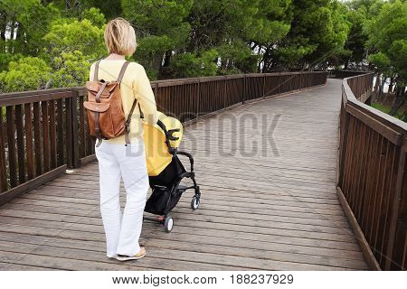 Mother with backpack pushing a stroller on wooden bridge while walking in a park