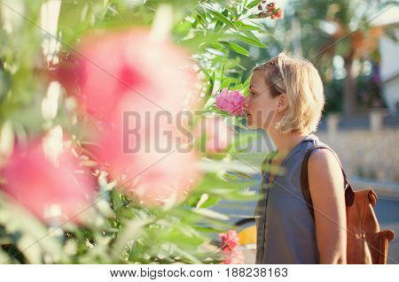 Young woman enjoying smelling aroma flowers outdoors on city street