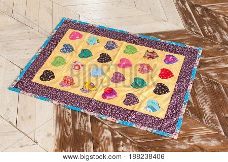 Color Patchwork quilt on a wooden background. Part of patchwork quilt as background. Handmade.