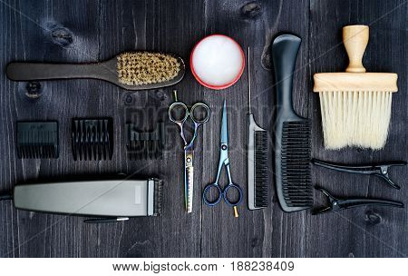 Hairdresser tools on wooden background. Top view on wooden table with scissors comb hairbrushes and hairclips free space. Barbershop manhood concept poster