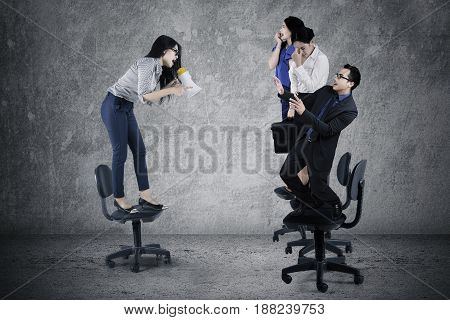 Picture of young businesswoman screaming to her teamwork with a megaphone while standing on the chair