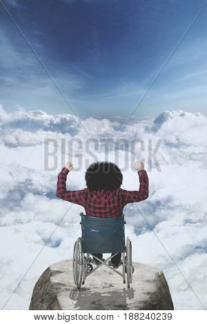 Rear view of disabled Afro man sitting in a wheelchair on the mountain peak while raising his hands above clouds on the sky
