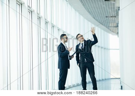 Two Businessmen Dicussing Building Changing  In Big Panoramic Hall