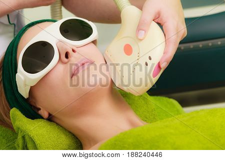 Medical cosmetology modern cosmetic devices concept. Woman wearing safety glasses getting laser treatment on her face in beautician