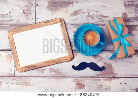 Fathers day background with photo frame coffee cup and gift box on wooden table. View from above. Flat lay
