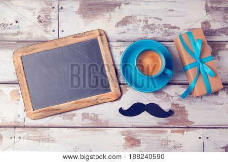 Fathers day background with chalkboard coffee cup and gift box on wooden table. View from above. Flat lay