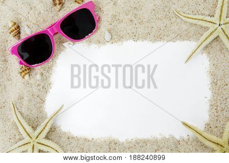 Close up of empty frame with white beach sand sun glasses seashells and starfish. Vacation concept