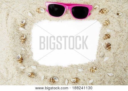 Empty frame made of white beach sand with a pink color sun glasses and seashells. Vacation concept