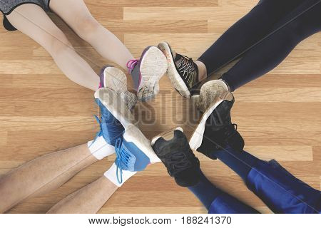 Top view of group of friends make foot circle with their legs and different shoes after workout on the wooden floor