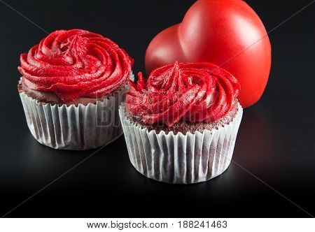 Two red cup cakes on and big red heart shape isolated on black background - Romantic background with text space - Conceptual love image