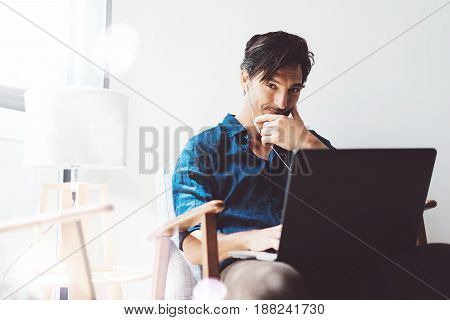 Smiling adult businessman working at office.Man using contemporary notebook on headphones while sitting in vintage chair.Blurred background. Horizontal