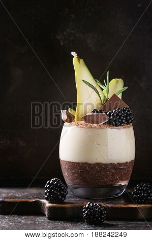 Dessert breakfast layered chia seeds, chocolate pudding, rice porridge in glass decorated by fresh blackberries, pear, cocoa powder on serving board over dark texture background.