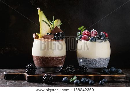 Various dessert breakfast layered chia seeds, chocolate pudding, rice porridge in glass decorated by fresh blackberries, sliced pear, cocoa powder. On wood serving board over dark texture background.