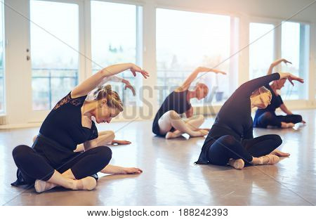 Fit Ballerinas Stretching On Floor In Class
