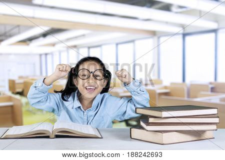 Primary student celebrating her success while sitting in the classroom with book on table