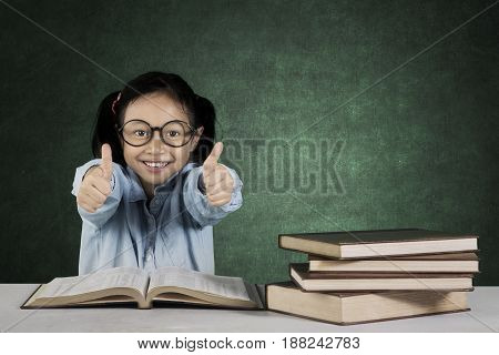 Portrait of primary student showing ok gesture while sitting in front of book on the table