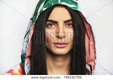 Young Woman Dressed In Hood Of Casual Jacket Looking At Camera