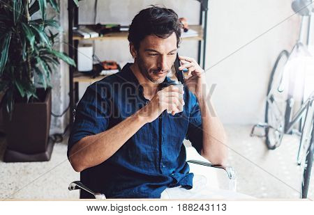 Closeup view of Hispanic elegant businessman working contemporary mobile computer while sitting at the wooden table at sunny office.Man talking on his mobile phone.Blurred background. Horizontal.