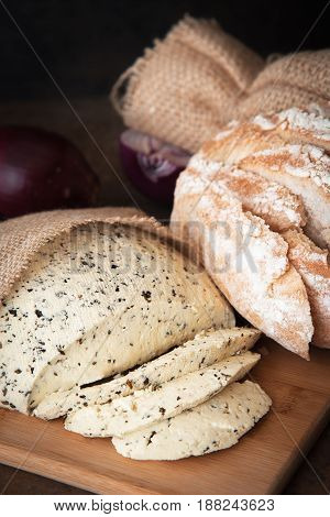 Homemade Organic Cheese with herbs basil on black stone slate background