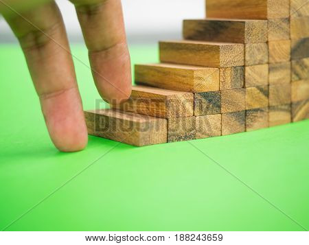 Finger is stepping on wooden block stair case