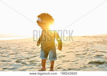 Cute little African-American girl toddler standing at the ocean on sandy shore in evening.