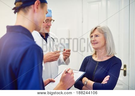 Medic Talking To Female Patient While Assistant Writing In Tablet